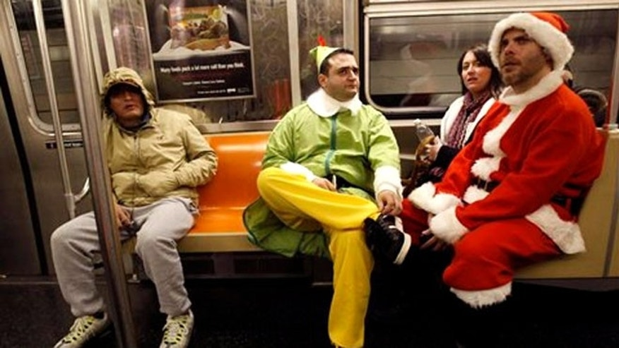 Dec. 11, 2010: John Paul, center, of Manhattan, dressed as an Elf and Michael Smallwood, of Brooklyn, dressed as Santa riding the E train downtown in New York.