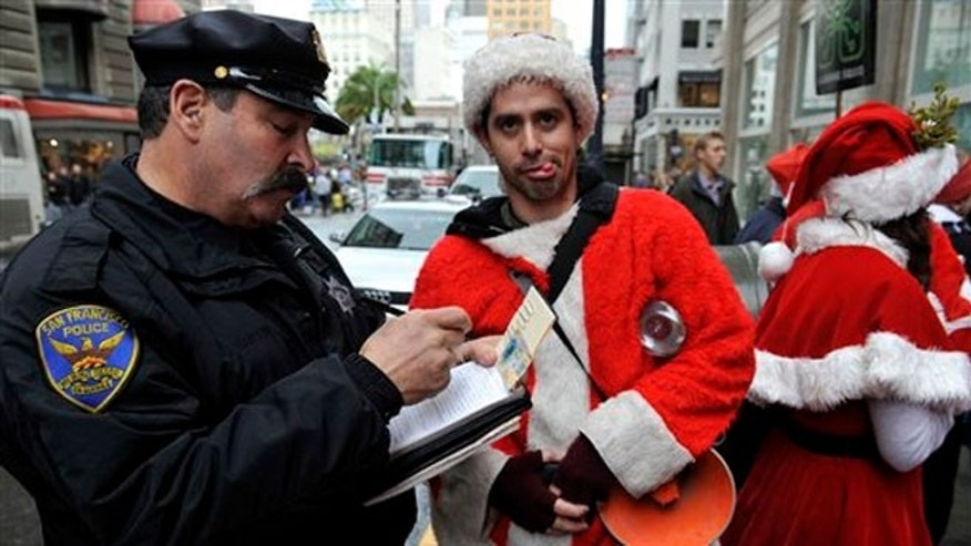 Dec. 10, 2009: A San Francisco Police officer giving a man dressed as Santa Claus an open container ticket during the Santacon pub crawl in downtown San Francisco.