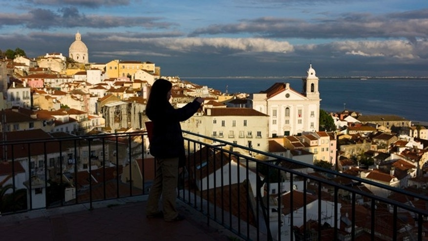 Dec. 18 2012: A tourist takes photos from a viewpoint overlooking Lisbon's Alfama neighborhood and the Tagus river.
