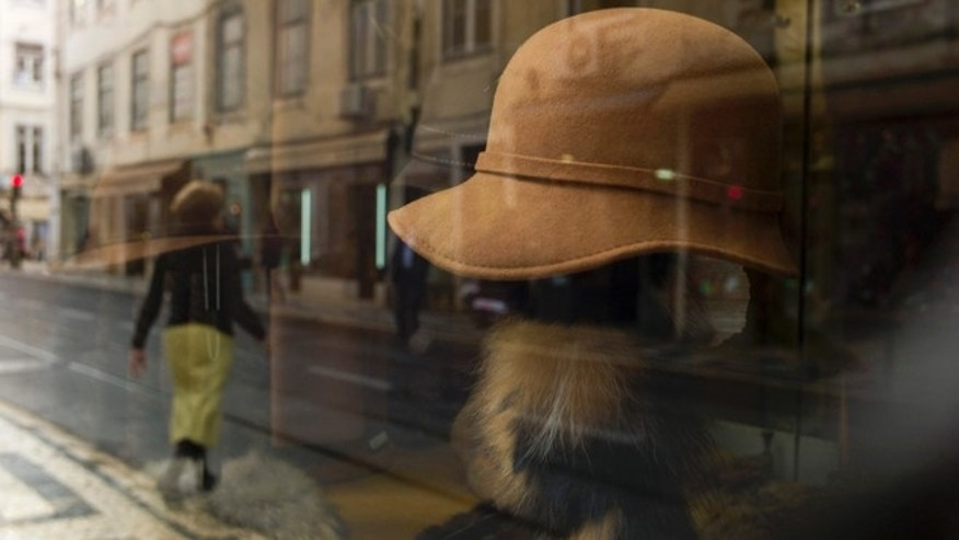 Dec. 21 2012: A women crossing the street is reflected on the window of a shop in Lisbon's Baixa neighborhood.