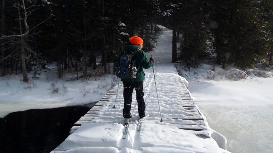 This December 2012 photo shows Lynn Dombek cross-country skiing over a bridge on the Lodge to Lodge trail between camps at the Appalachian Mountain Club's backcountry wilderness lodge near Greenville, Maine.