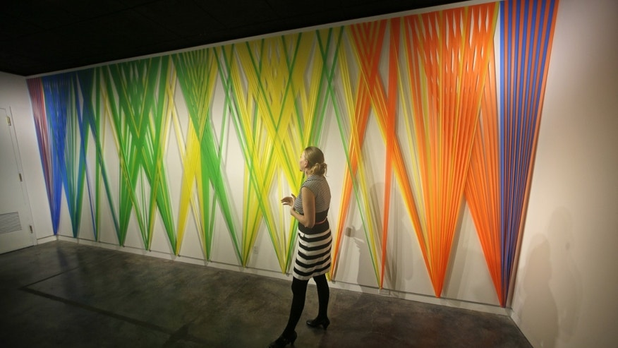 Jan. 9, 2013: Sarina Ehrgott, marketing director, walks pass  Megan Geckler exhibit at the Utah Museum of Contemporary Art.