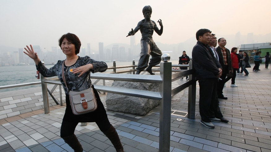 Jan. 11, 2013: Mainland Chinese tourists pose in front of a bronze statue of the Hong Kong martial art actor Bruce Lee on the Avenue of Stars, the city's version of the Hollywood Walk of Fame in Hong Kong.