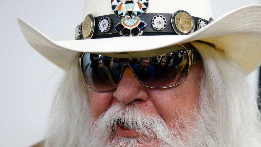 Jan. 29, 2013: Reporters are reflected in the sunglasses of Leon Russell as he answers a question at a news conference in Tulsa, Okla.