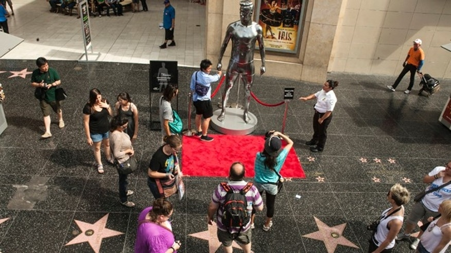 Aug. 17, 2012: Tourists take photos with a 10-foot statue created and modeled after English soccer star David Beckham displayed in the Hollywood section of Los Angeles.