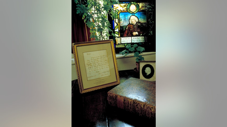 This March 17, 2009 photo released by VisitBritain shows shows a letter written by Samuel Johnson and a copy of the dictionary he wrote, which was published in 1755, beneath a stained glass plaque at Dr. Johnson's House, a small museum in the 300-year-old townhouse where he lived in London.