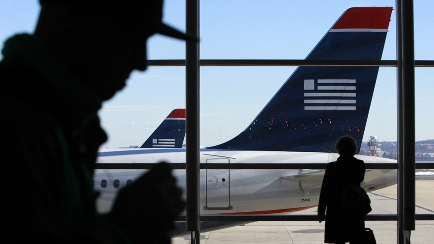 FILE - In this Sunday Dec. 27, 2009 file photo, passengers walk past US Airways planes at Reagan National Airport in Washington.