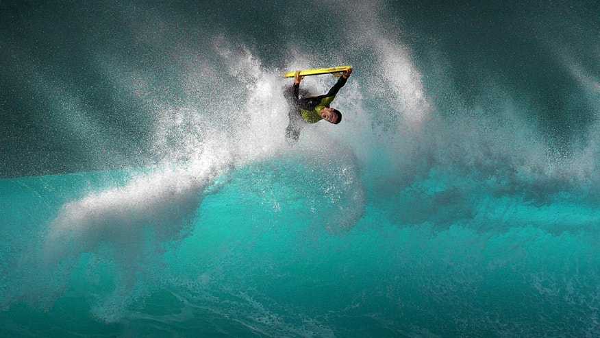 A boogie boarder rides a wave on the Banzai Pipeline off Ehukai Beach Park on the North Shore of O'ahu, Hawaii, on Monday Feb. 18, 2013. (AP Photo/ Frederic Larson)