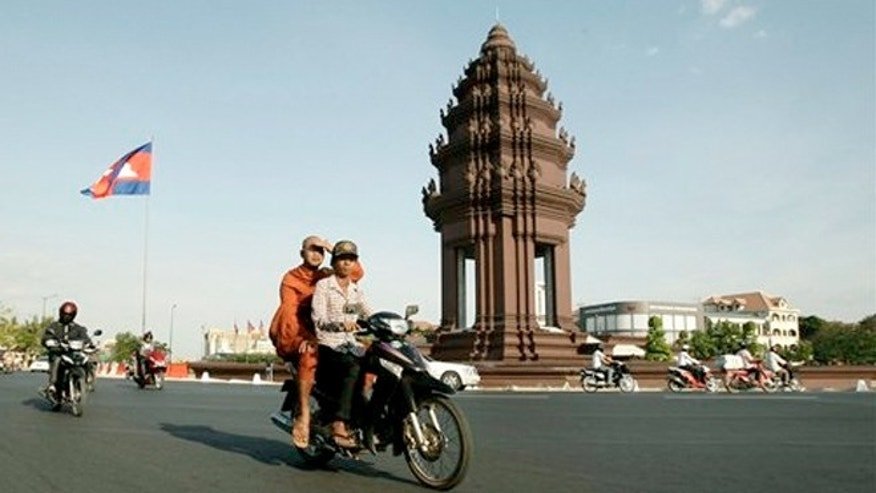 Feb. 25, 2013: A Cambodian motorists, transports a Buddhist monk, center, while driving past Independence Monument, in Phnom Penh, Cambodia.