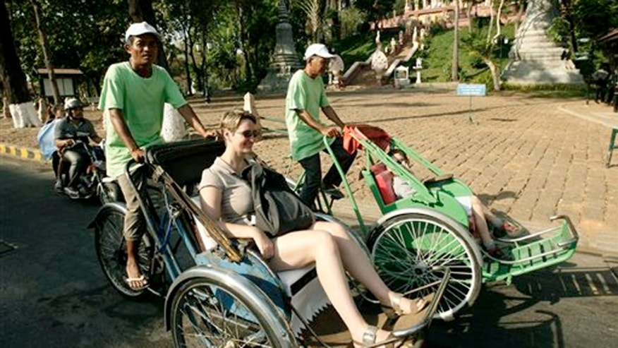Feb. 26, 2013: Tourists ride on three-wheeled pedicabs while passing an entrance of Wat Phnom, in Phnom Penh, Cambodia.