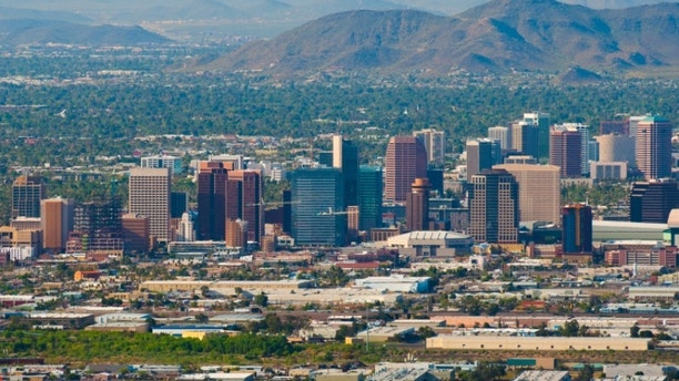Aerial view of the Phoenix downtown skyline with the midtown skyline behind as well as North Mountain and other mountains in the background.