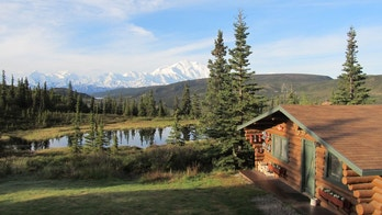 The original hand-crafted cabin at Camp Denali (built in the early 1950s) with Mt. McKinley showing in the background.