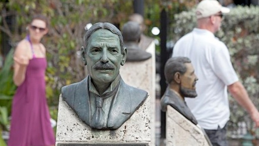 March 13, 2013: Visitors walk in the Key West Historic Memorial Sculpture Garden behind a bust of Henry Flagler in Key West, Fla.