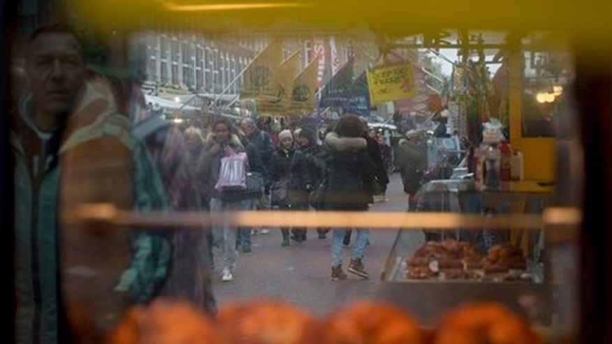 March 20, 2013: People through and reflected in a stand with grilled chickens at Albert Cuyp market, Amsterdam, Netherlands.