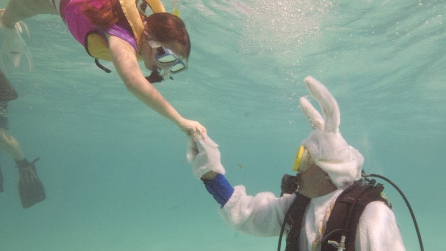Spencer Slate, costumed as a scuba diving Easter bunny, hands a hard-boiled egg to Quinn Vanischak.