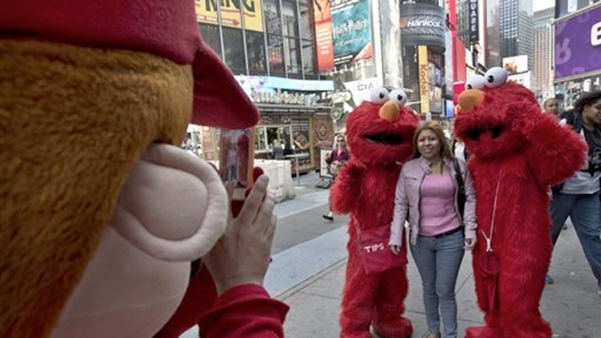 April 9, 2013: A Super Mario character, left, uses a woman's mobile phone camera to photographer her with a pair of Elmo characters.