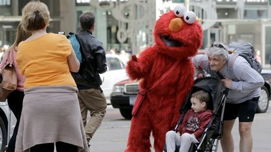 April 9, 2013: An Elmo character poses for photos in New York's Times Square.