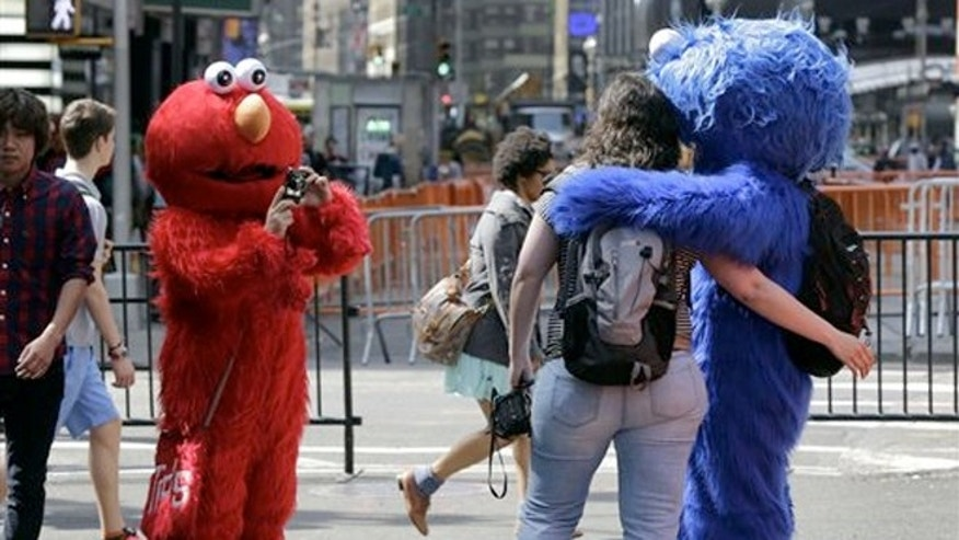 n Elmo character, left, uses a woman's camera to photographer her April 9, 2013: An Elmo character uses a woman's camera to photographer her with a Cookie Monster character.