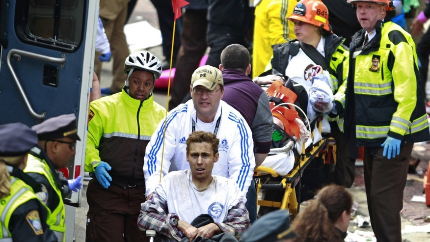 Medical workers aid injured people at the finish line of the 2013 Boston Marathon following two explosions Monday, April 15.