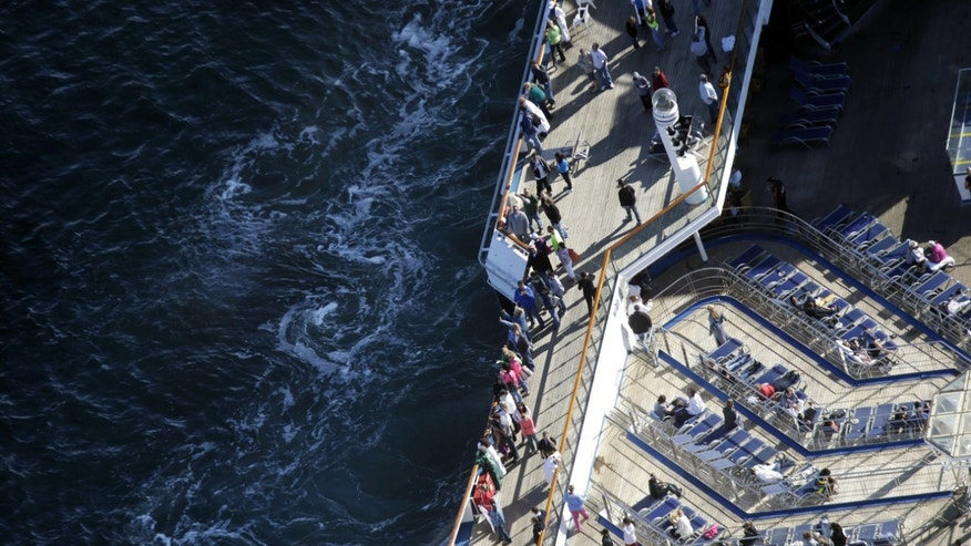 Passengers stand on the upper deck of the disabled Carnival Lines cruise ship Triumph as it is towed to harbor off Mobile Bay, Ala., Thursday, Feb. 14, 2013.  The ship with over 1,000 passengers aboard has been idled for nearly a week in the Gulf of Mexico following an engine room fire. (AP Photo/Gerald Herbert)
