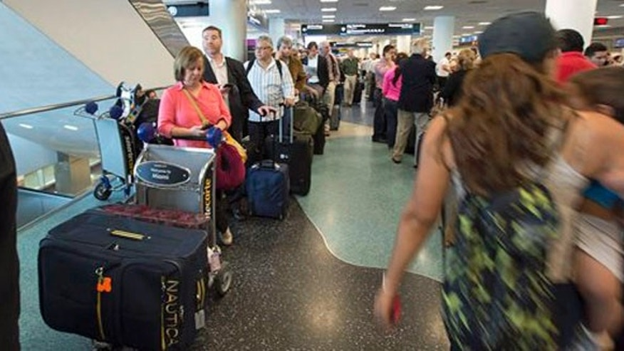 People stand in long lines at the American Airlines ticketing counter at Miami International Airport, Tuesday, April 16, 2013 as they try to make arrangements for new flights.