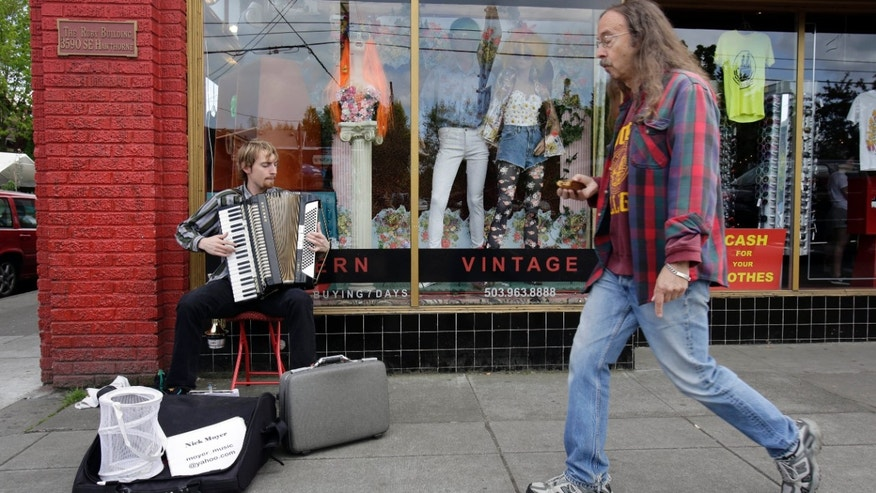 This April 30, 2013, image shows a street musician and passerby outside a vintage clothing store on Hawthorne Boulevard in Portland, Ore.