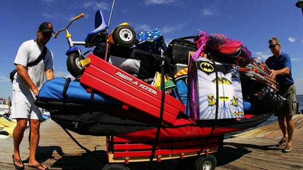 FIRE ISLAND, NY - SEPTEMBER 5: Mirk Davis (in front) gets help from a friend as he pulls his wagon full of vacation supplies on September 5, 2005 at Ocean Beach on Fire Island off the coast of Long Island in New York.  Ferry service to Fire Island began in 1856; passengers could take the Long Island Railroad from Brooklyn to Thompson (now Brentwood), get a stage to Islip, and get on the waiting ferry. Nearly 150 years later, transportation to Fire Island is basically the same. Although there are more ferries from different locations, you do have to take a ferry to get to most parts of Fire Island. Fire Island,  which is the only developed barrier island in the United States without roads, is located 45 minutes outside of New York City, just a 30 minute ferry ride across the Great South Bay. Fire Island is a premier getaway spot for families and friends. Sand dune beaches rollout into the Atlantic Ocean on the south side of the island, while the north side has dining and bars overlooking the bay. (Photo by Ezra Shaw/Getty Images)
