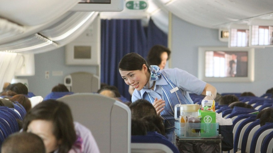 A cabin attendant serves to passengers on a Boeing 787 plane of the All Nippon Airways.