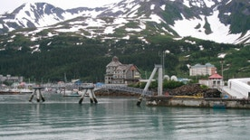 This photo taken July 9, 2012, shows the tiny community of Whittier, Alaska, where most of the 180 year-round residents live in the tall condo in the back, a former Army garrison. Most cruise ship passengers leave for Anchorage once their ships dock in Whittier, but those who stay can kayak, hike trails or visit a few tourist shops, cafes and restaurants.  (AP Photo/Mark Thiessen)