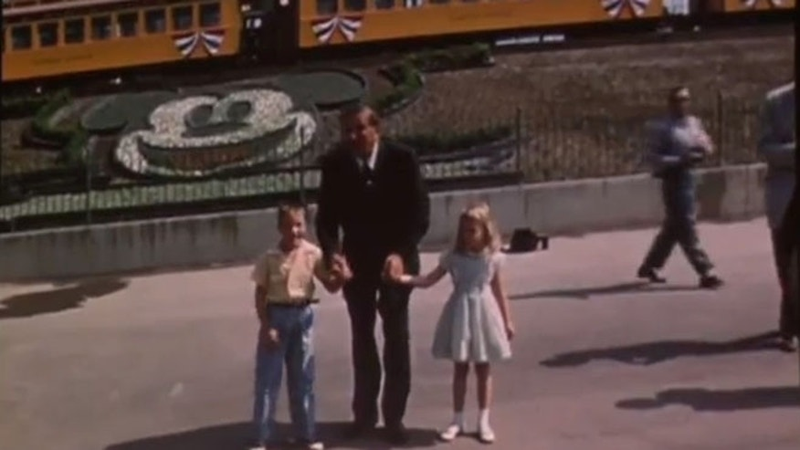 Walt Disney stands with the first children to enter Disneyland.