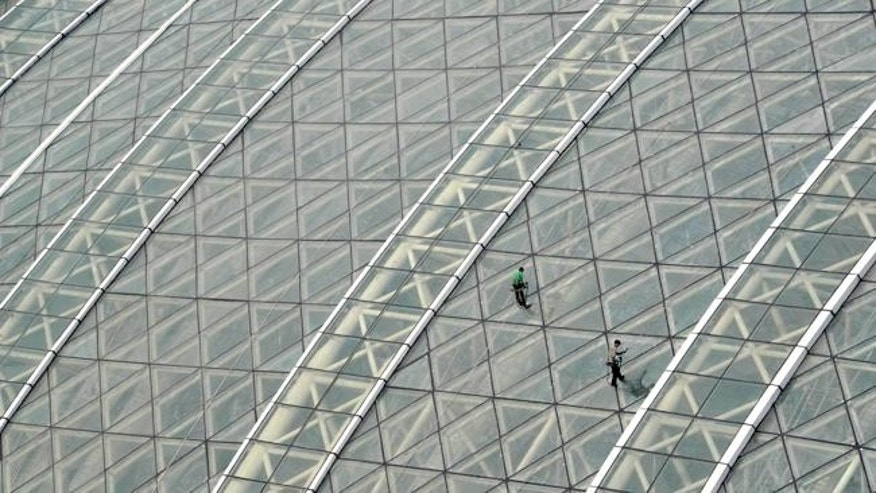 Workers clean the glass roof of the New Century Global Center building.