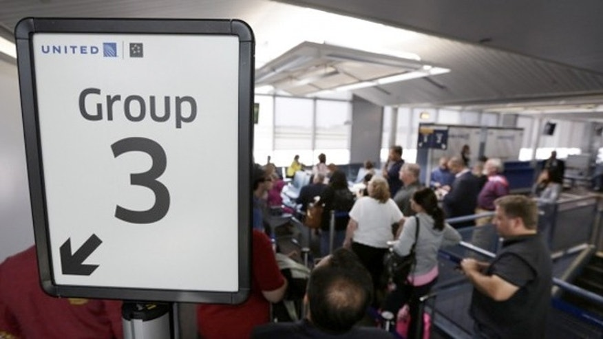 May 8, 2013: Groups of passengers wait at a United Airlines gate to board a flight in separate numbered lanes at O'Hare International Airport.