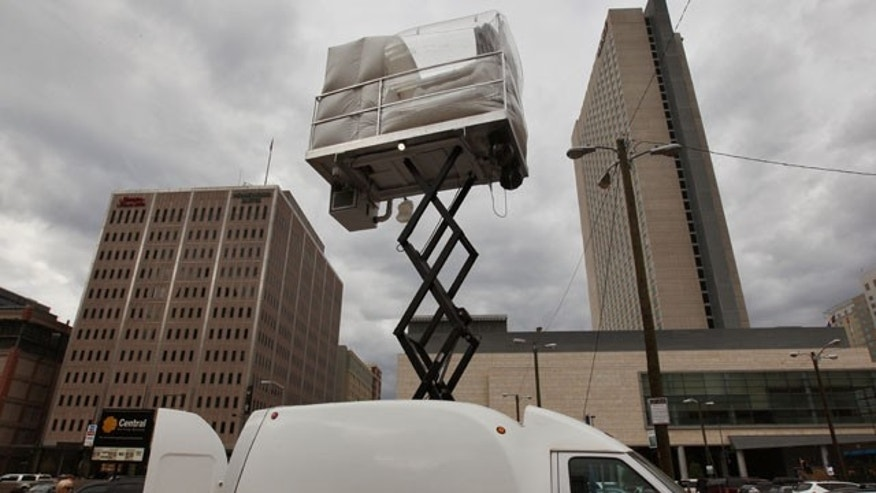 July 25, 2013: A hotel room made of aluminum and inflated vinyl is held aloft by a van-mounted scissor lift, on promotional display in a parking lot in downtown Denver. Architectural artist Alex Schweder created the 5 by 7 foot room atop a van for the Biennial of the Americas in Denver. For $50,000, a guest would get one weekend night in the puffy space, plus lots of extras including a diamond pendant and earring set, two iPod Nanos and a dance party for 100 people in a ballroom of The Curtis Hotel. (AP Photo)