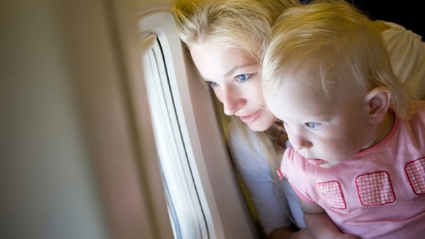 mother and child look through the window of the airplane