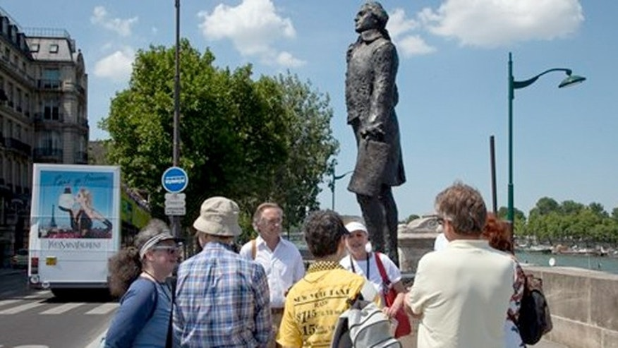 July 19, 2013: Tourists gather around the Thomas Jefferson Statue next to Musée d'Orsay during a Guided Tour around the main spots of the Revolutonary-era American presence on Paris' left bank, in Paris, France.