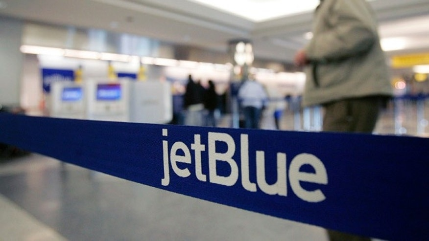 FILE - In this Wednesday Feb. 1, 2006, file photo, a pedestrian makes his way to the e-ticket counter of JetBlue at New York's LaGuardia Airport. Starting  in 2014,  JetBlue, the all-coach airline, plans to offer 16 lie-flat seats on flights between New York and Los Angeles and San Francisco. It's the first time the egalitarian carrier will have a second class of service. (AP Photo/Frank Franklin II, File)