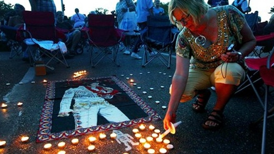 Aug. 15, 2013: Elvis Presley fan Jill Gibson lights candles outside Graceland, Presley's home, before the annual candlelight vigil on Thursday, in Memphis, Tenn.