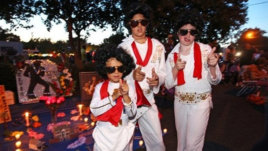 Aug. 15, 2013: Nicholas Woodlief, 7, left, his sister Annabelle Woodlief, 11, and friend, Eli Crain, 11, right, strike an Elvis Presley pose at Graceland.