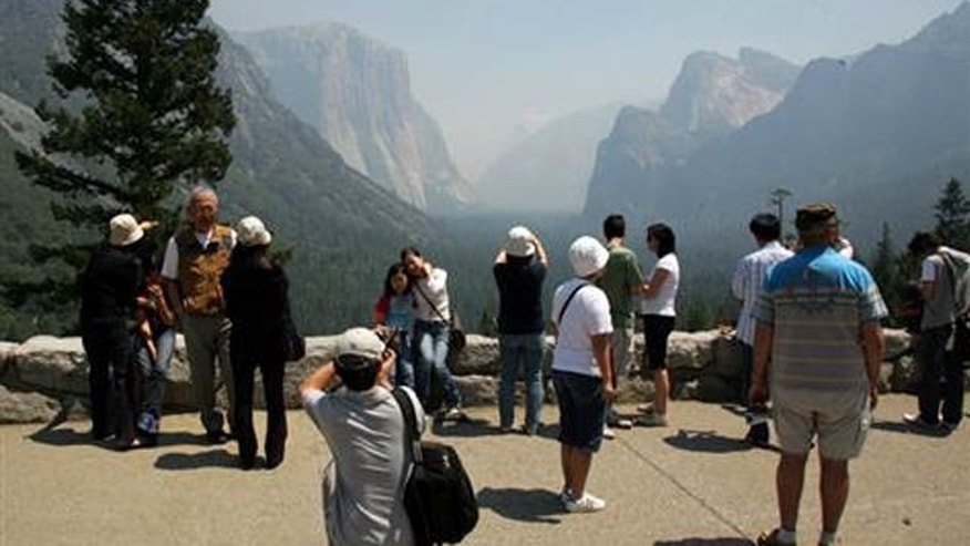 Despite the haze from the nearby wildfire, tourists take photos of El Capitan, background left, and the Half Dome, background right, on Monday in Yosemite, Calif.