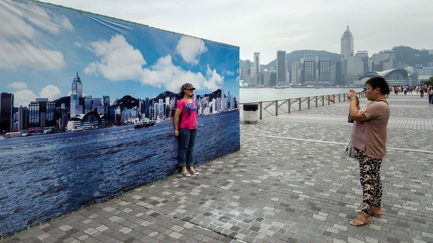 A tourist has her picture taken during a cloudy day in front of a billboard featuring photos of the city skyline with a clear sky in Hong Kong on August 30, 2013.