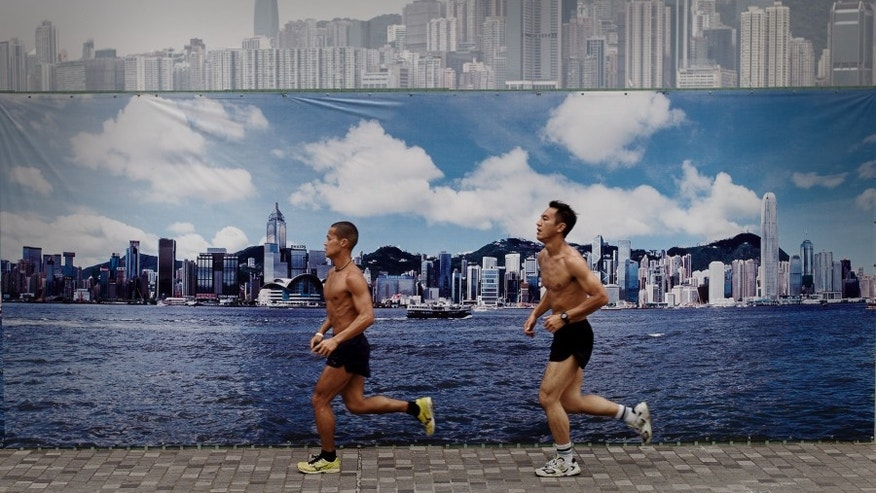 Two men jog past a billboard featuring photos of the city skyline with a clear sky on a cloudy day in Hong Kong on August 30, 2013.