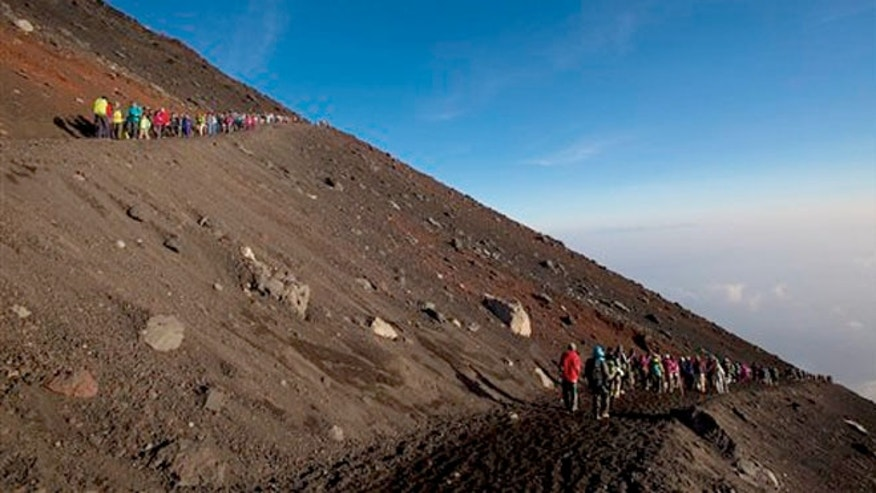 Aug. 11, 2013:  Hikers make their way down from the summit of Mount Fuji after watching the sunrise form the top.