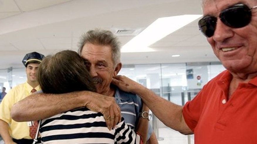 Sept. 11, 2013:  Benito Perez, center, is greeted by his friends Rogelia Ventura and Luis Ventura, right, at his arrival at Miami International Airport, in Miami.