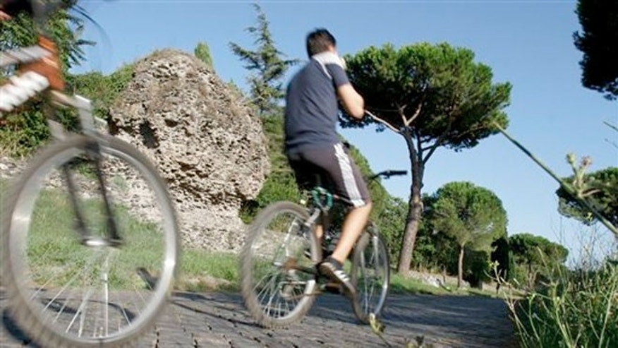 People cycle past ruins along the Appia Antica, the ancient Roman Appian Way, in Rome.