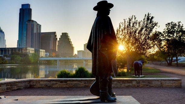 The statue of Stevie Ray Vaughan stands on the shores of Lady Bird Lake, with the skyline of Austin behind him.