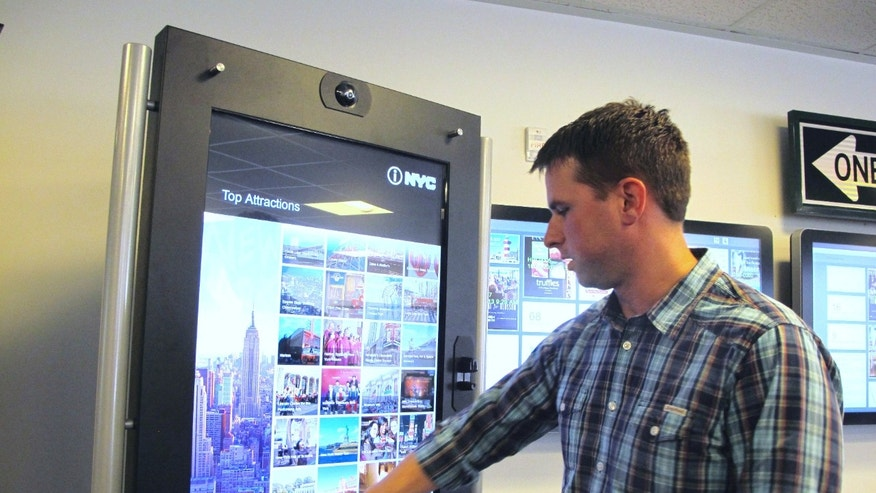 ADVANCE FOR SUNDAY, OCT. 27 AND THEREAFTER- In this Oct. 25, 203 photo, Chad Priest, the chief operating officer for City Corridor, demonstrates a touch screen interactive visitor kiosk in the company's offices in North Charleston, S.C. The interactive kiosk allows visitors to click and print out everything from maps to menus and buy tickets for attractions. (AP Photo/Bruce Smith)