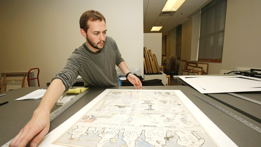 "Oct. 23, 2013 photo, Jeremy Stone frames a Billy Ireland comic strip called ""The Passing Show""  at the Billy Ireland Cartoon Library & Museum in Columbus, Ohio."