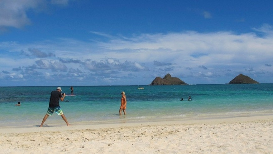 This Oct. 29, 2013 photo shows tourists on Lanikai Beach in Kailua, Hawaii. The Kailua Neighborhood Board is upset about a thriving industry of illegal bed-and-breakfast and vacation rentals and is asking the state tourism agency to stop encouraging visitors to stay overnight in their town.