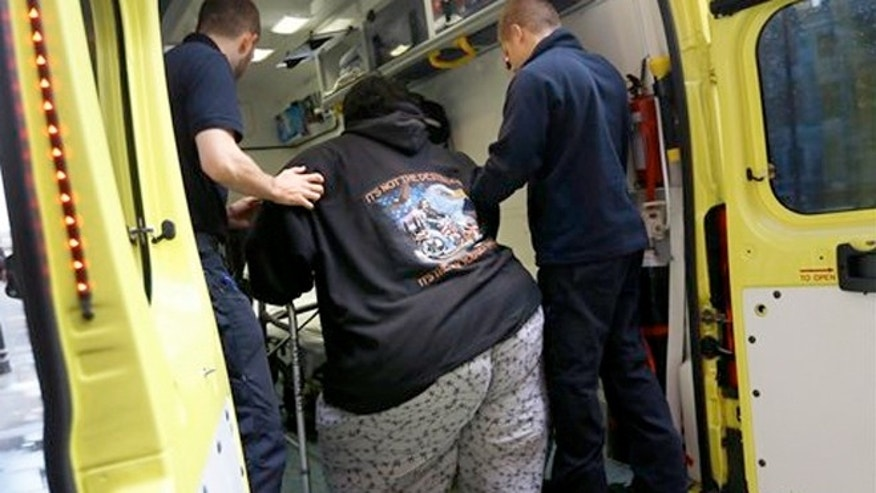 Nov. 20, 2013: Kevin Chenais, center, is assisted by ambulance staff onto an ambulance at St Pancras in London.