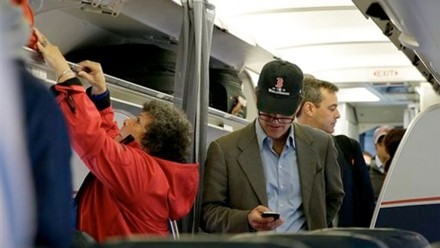 FILE -A passenger checks his cell phone while boarding a flight, in Boston.